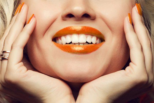 Fotografia di una giovane ragazza rappresentante il tipico sorriso con rossetto appoggiato sulle mani dei Centri Smile