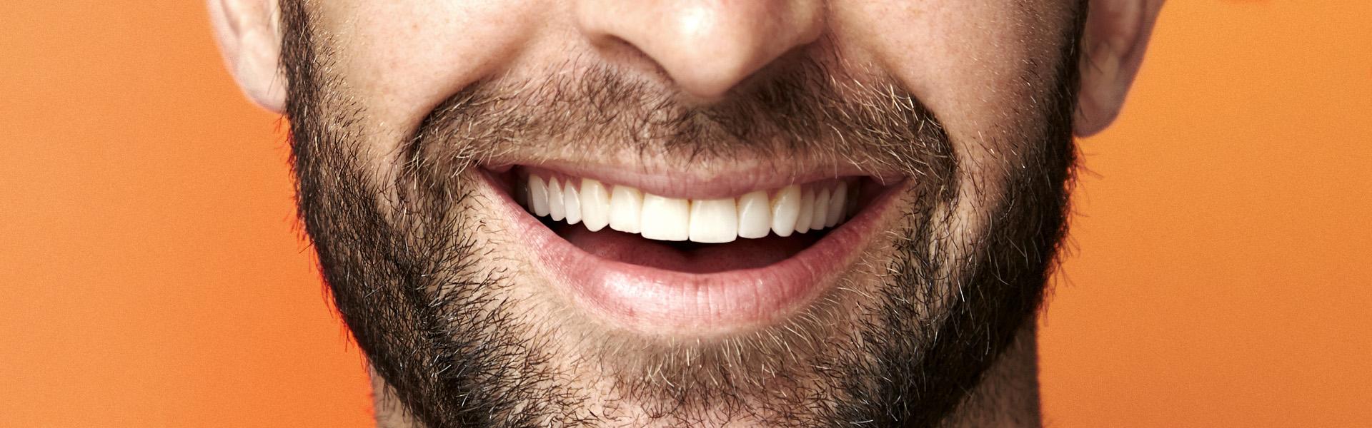 Sorriso smagliante di un giovane uomo dopo un trattamento presso i Centri Smile