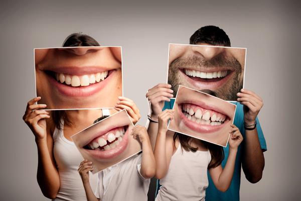 Famiglia felice presso i Centri Smile, tra le mani diversi poster rappresentanti sorrisi