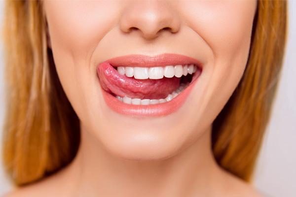 Ragazza soddisfatta passa lingua tra i denti al termine di un trattamento di igiene orale presso i Centri Smile per provare la sensazione di un sorriso pulito