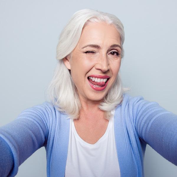 Signora soddisfatta con lingua tra i denti al termine di un trattamento presso i Centri dentistici Smile