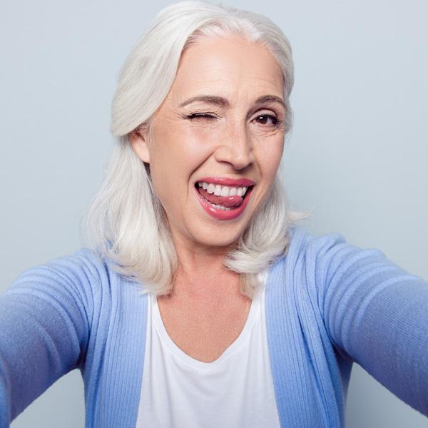 Signora soddisfatta con lingua tra i denti al termine di un trattamento presso i Centri Smile