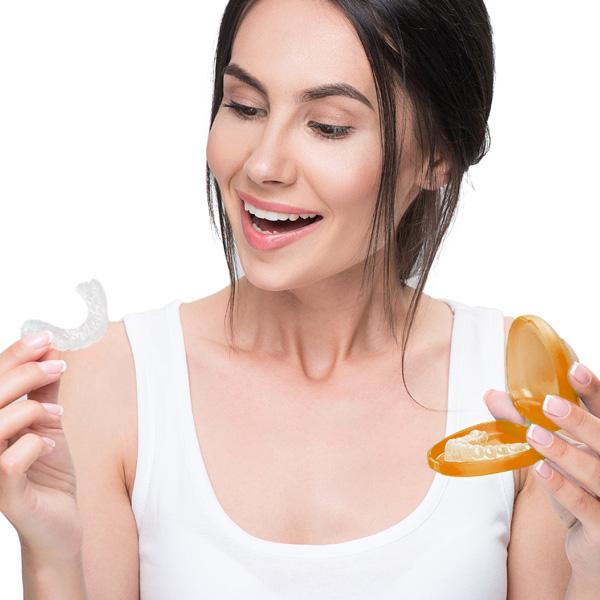 Ragazza con in mano un sistema di allineatori trasparenti preso nei Centri Smile, per iniziare un trattamento di ortodonzia